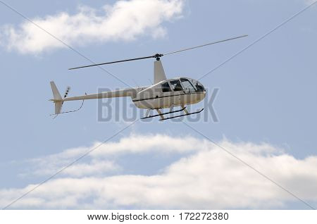 Private helicopter flying in blue cloudy sky