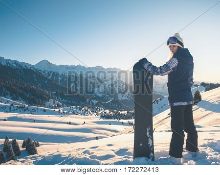 Adventure to winter sport. Snowboarder girl on the background of high mountain Alps in Switzerland.