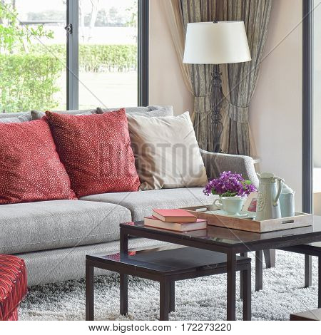 Modern Living Room Design With Red Pillows On Sofa And Dacorative Tea Set On Table