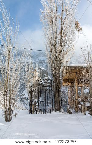 A village house and a metal fence on the road to Geghard Monastery unique architectural construction and a UNESCO World Heritage in Armenia on cold winter sunny day.