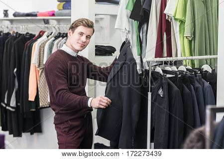 happy young man in shirt choosing jacket in mall or clothing store