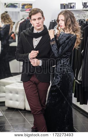 Very attractive, young and fashionable couple shopping clothes.