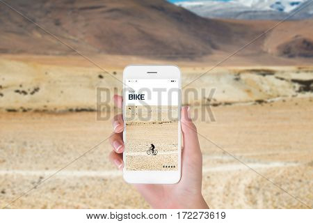 woman using her smart phone for searching the travel information of bike cycling through remote area on rugged road in Himalayan. Traveling concept Himalayan range blurry background.
