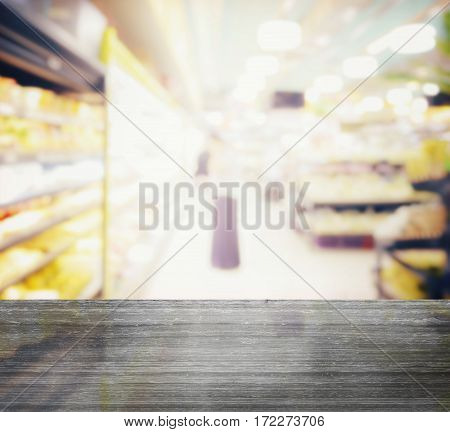 Black Granite Table Top And Blur Of Supermarket With Miscellaneous Product On Shelves
