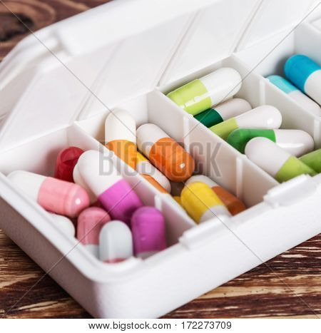pills of different colors in a box from under the medicines