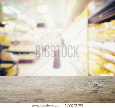 Wooden Table Top With Blur Of Supermarket With Miscellaneous Product On Shelves