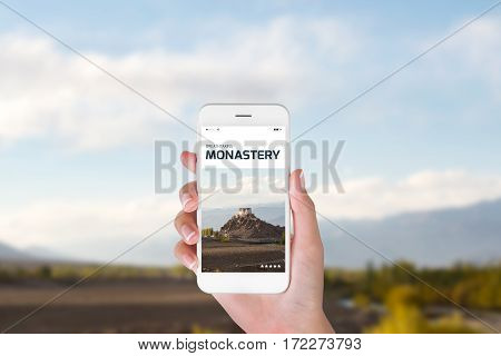 woman using her smartphone for searching the travel information of beautiful Stakna monastery in the Himalayan range Leh Ladakh India. Traveling concept Beautiful Monastery blurry background.