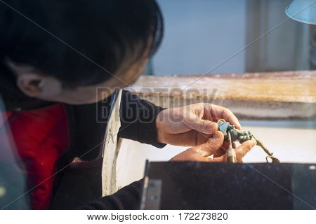 BEIJING December 28 2016: Close up of a Chinese man makes a carving jade
