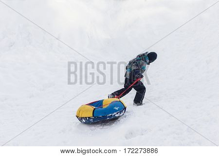Happy child walks with tubing in the winter frosty day.