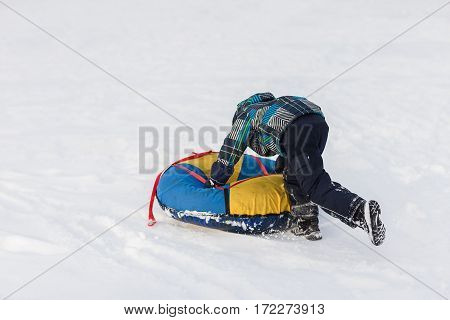 Happy child pushes the tubing in the snow in the winter frosty day.