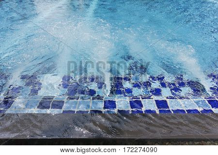 Inflowing water jet into a pool with blue tiles