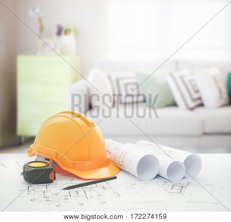 architectural blueprint with safety helmet and tools over cozy sofa with geometric pattern pillows and green sideboard in living room