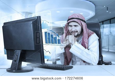 Image of middle eastern businessman looks confused with a virtual declining business graph on the monitor