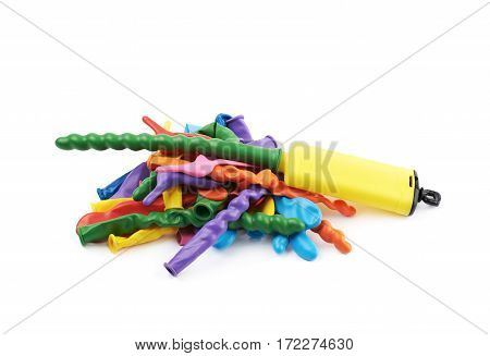 Pile of multiple colorful unblown balloons with a yellow pump over it, composition isolated over the white background