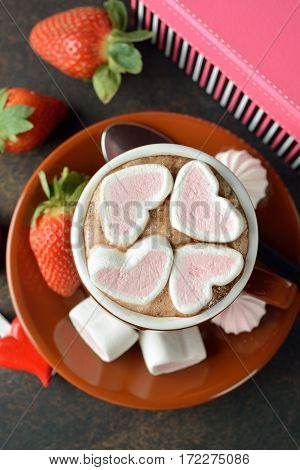 Cup of cocoa with marshmallows on a brown background top view
