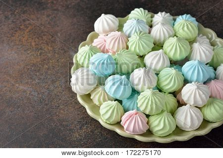 Multicolored meringue on a brown background close up
