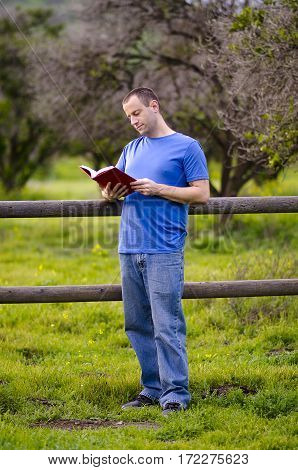 Reading outside in nature alone leaning against a wooden fence. Enjoying a leisure activity.