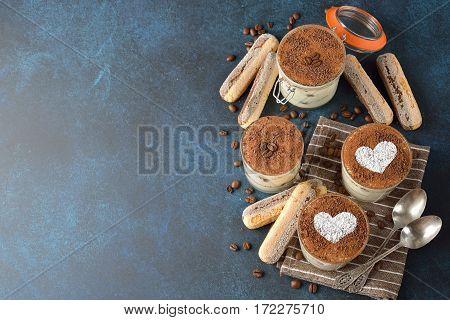Traditional Italian dessert tiramisu on a blue background
