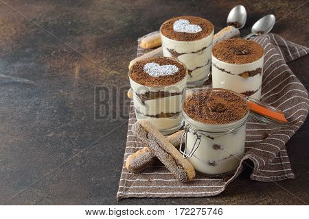 Traditional Italian dessert tiramisu on brown background