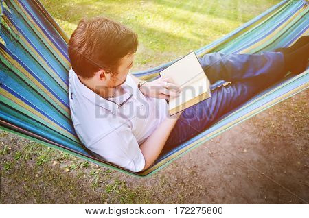 A man in a hammock reads a book in the park