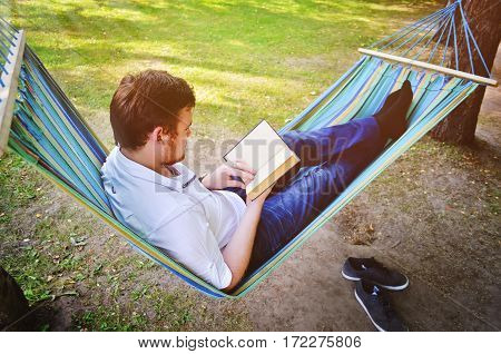 A handsome man reads a book in the park