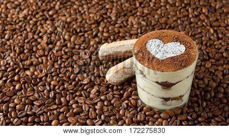 Traditional Italian dessert tiramisu on coffee beans