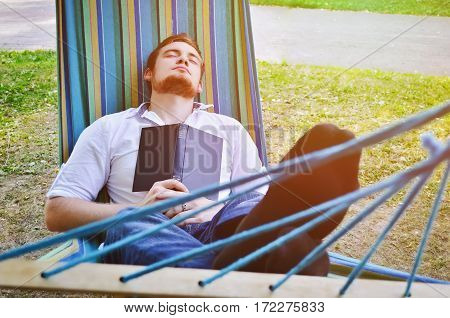 Sleeping man in the hammock in the park
