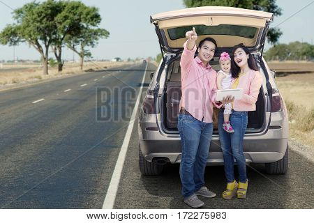 Asian family enjoying road trip standing behind a car while looking at something and holding digital tablet on the street