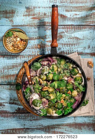 Roasted sprouts in a cast iron frying pan on a wooden table top view