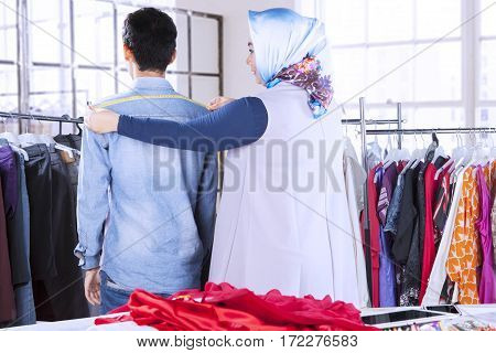 Female designer measuring her male model by using measuring tape while standing in her workplace