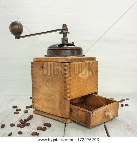 A photo of a vintage coffee grinder with coffee grains and a place for text