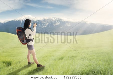 Female hiker taking pictures of mountain with digital camera in the meadow