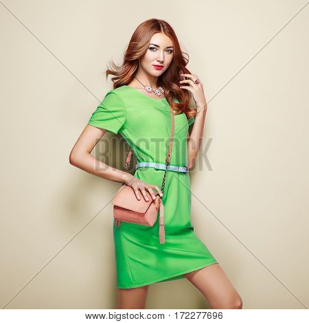 Blonde young woman in elegant green dress. Girl posing on a beige background. Jewelry and hairstyle. Girl with handbag. Fashion photo