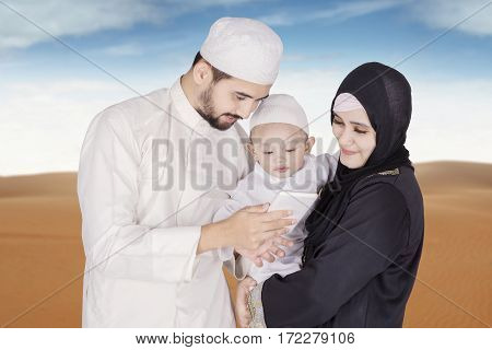 Happy muslim family watching video on smartphone while standing on the desert