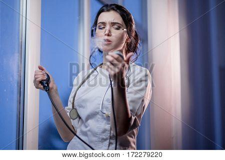 Brunette sassy female nurse in uniform smoking a cigarette measures the blood pressure