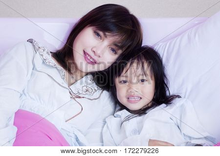 Happy little girl and her mother lying on the bedroom while wearing pyjamas and smiling at the camera