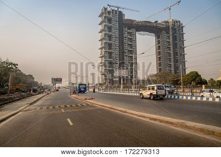 KOLKATA, INDIA -FEBRUARY 12, 2017: City road connector traffic on E.M. Bypass with a building under construction. Photograph taken near Science City Kolkata on a weekend morning.
