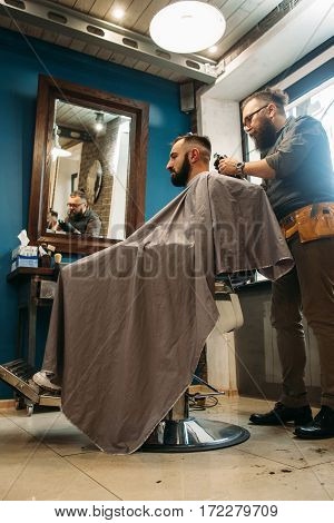 Man cut hair at barber shop free space. Side view on modern confident businessman at beauty salon. Fashion, style, glamour, business concept
