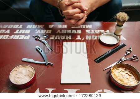 Blank card with barber tools on table free space. Side view on gules workplace with hairstyling instruments and hands of sitting man on background, Work, barbershop, manhood concept