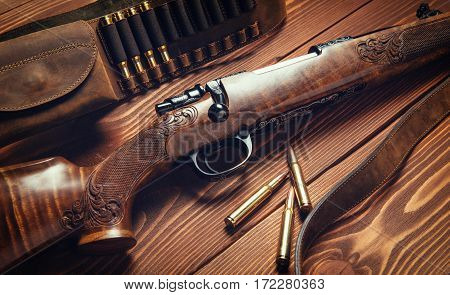 Hunting equipment on old wooden background and bullets.