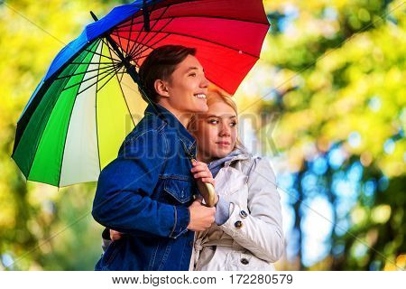 Autumn couple walking park. Fall friends walk under rain umbrella. First date of two young people in rainy day.
