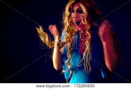 Frightened woman screaming with fear indoor at halloween night. Horror. Girl with tousled hair bawl covers her mouth with her hands black background.