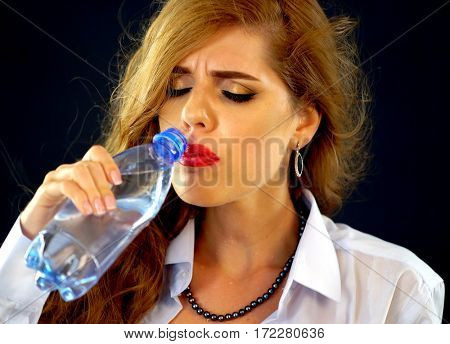 Sensitive teeth woman drinking cold water from bottle . Sudden toothache of thirsty girl in business suit drink . Heat in office. Lady with closed eyes guzzles on black background.