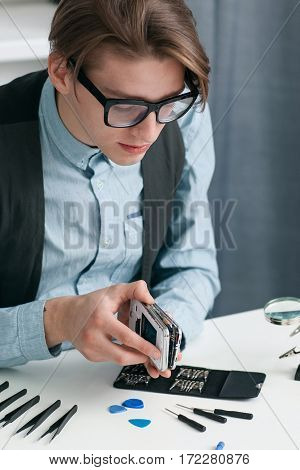 Man disassembling smartphone in repair shop. Young serious repairman separating mobile phone parts for diagnostics. Electronic fixing, modern technology, small business concept
