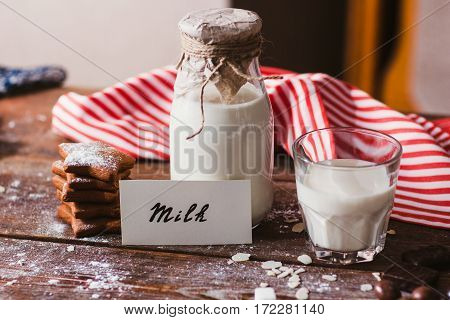 Bottle and glass of milk with cookies on table. Natural organic drink with sweets ready for eating, tasty snack for children. Farming, countryside, healthy lifestyle concept