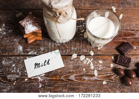 Healthy breakfast for children on wood flat lay. Top view on messy wooden kitchen table with bottle and glass of milk, cookies and chocolate, and card with word milk