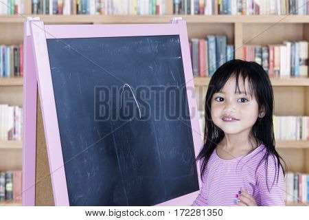 Cute little girl smiling at the camera with empty chalkboard in the library