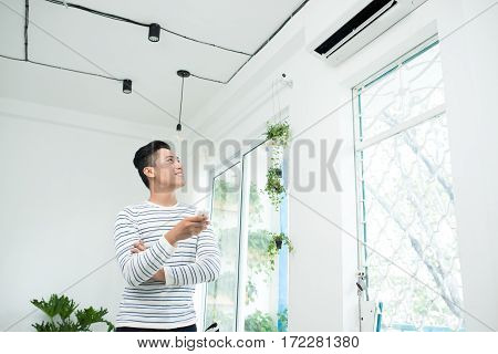 Asian man is turning air condition by remote control and smiling