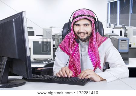 Male operator wearing traditional clothes while working with a computer and headphone in the office