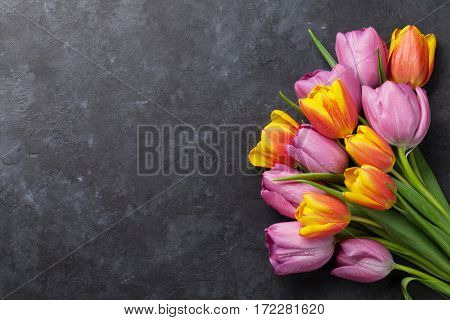 Fresh colorful tulip flowers on dark stone table. Top view with copy space